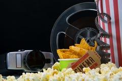 Schwarzer Hintergrund mit einem, mit einem Satz Imbissen in der Bar für aufpassende Filme, Retro- Kamerarecorder und Popcorn zu n stockfotos