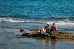 Schwarzer Hund und zwei Young Boys gesetzt auf Riff nahe Meer Lizenzfreies Stockfoto