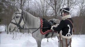 Schwarzer Husar sattelt sein Pferd im Winter stock video