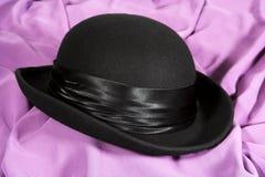 Schwarzer Hut auf einem lila backgroun Stockfotografie