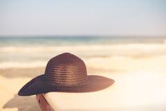 Schwarzer Hut auf Strand-Stuhl auf dem tropischen Sand-Strand Sun, Sonnendunst, greller Glanz Kopieren Sie Platz Lizenzfreie Stockfotos