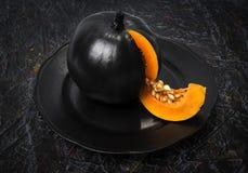 Schwarzer Kürbis auf einem Schwarzblech, auf einem abstrakten Hintergrund stockfotos