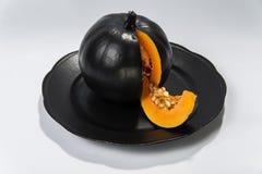 Schwarzer Kürbis auf einem Schwarzblech auf einem hellen Hintergrund lizenzfreies stockfoto
