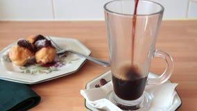 Schwarzer Kaffee, der in einen Glasbecher ausgelaufen wird stock video