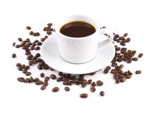 Schwarzer Kaffee in einem Becher mit UntertassenKaffeebohnen sind zerstreute ISO Stockfoto