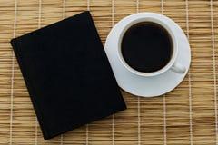 Schwarzer Kaffee in einer Schale auf einer Untertasse auf die Oberseite mit einem Buch Stockbild