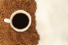 Schwarzer Kaffee in einer Schale mit Gefolge des gemahlenen Kaffees und des Zuckers Die Ansicht von der Oberseite stockfoto
