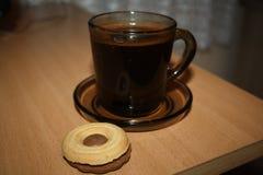 Schwarzer Kaffee in einer schwarzen glasigen Schale mit Keks Lizenzfreie Stockfotografie