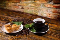 Schwarzer Kaffee mit feinschmeckerischem Gebäck und Minze Stockfotos