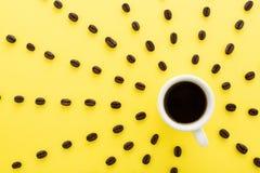 Schwarzer Kaffee mit Sonnenstrahlen von Kaffeebohnen auf Pastellgelbrückseite Stockfotografie