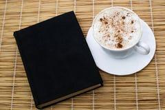 Schwarzer Kaffee mit Zimt in einer Schale auf einer Untertasse auf die Oberseite mit einem Buch Lizenzfreie Stockfotografie