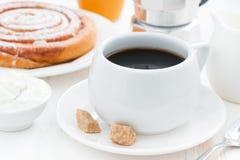 Schwarzer Kaffee, süßes Brötchen und Creme Stockfotografie