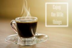 Schwarzer Kaffee und eine Anmerkung genießen die Kleinigkeiten Lizenzfreie Stockfotografie