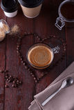 Schwarzer Kaffee unter geformten Kaffeebohnen des Herzens stockbild