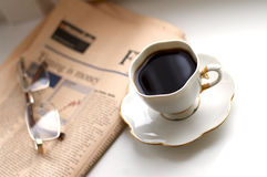 Schwarzer Kaffee, Wirtschaftszeitung und Gläser Lizenzfreies Stockfoto
