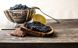 Schwarzer Kaviar in einer silbernen Schüssel mit Brot und Zitrone auf einem hölzernen Hintergrund Lizenzfreies Stockbild