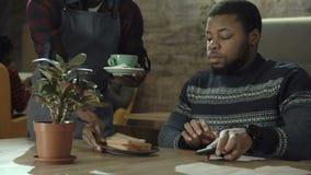 Schwarzer Kellner, der einen Mannkaffee und -erfrischungen dient stock video footage