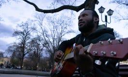 Schwarzer Kerl, der eine Gitarre spielt und glückliches Sitzen in einer Bank eines Parks singt lizenzfreie stockfotografie