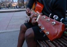 Schwarzer Kerl, der eine Gitarre spielt und glückliches Sitzen in einer Bank eines Parks singt lizenzfreies stockfoto
