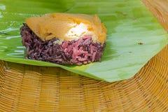 Schwarzer klebriger Reis mit dem Vanillepudding, eingewickelt in der Banane verlässt Stockfoto