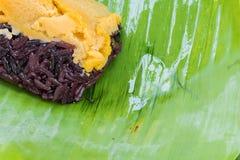Schwarzer klebriger Reis mit dem Vanillepudding, eingewickelt in der Banane verlässt Stockbild