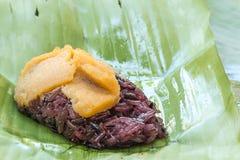 Schwarzer klebriger Reis mit dem Vanillepudding, eingewickelt in der Banane verlässt Lizenzfreie Stockfotos