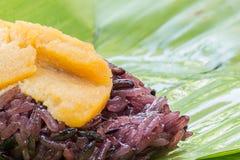 Schwarzer klebriger Reis mit dem Vanillepudding, eingewickelt in der Banane verlässt Lizenzfreie Stockbilder