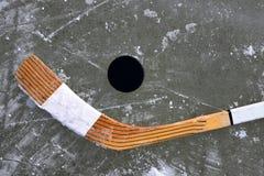 Schwarzer Kobold und Hockeyschläger, die auf einer Eisbahn liegt lizenzfreie stockfotos