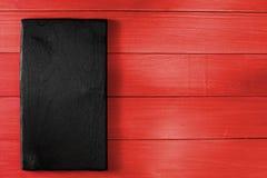 Schwarzer kochender Schreibtisch auf rotem Holztisch lizenzfreies stockbild