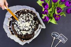 Schwarzer Kuchen auf schwarzem Hintergrund mit Blumen Stockfoto