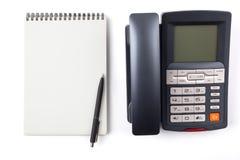 Schwarzer Kugelschreiber an einem Notizbuch und an einem digitalen Telefon Stockbild