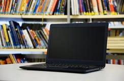Schwarzer Laptop auf dem Tisch, Bücherregale mit Büchern im Hintergrund Stockbilder