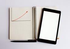 Schwarzer Laptop liegt auf dem geöffneten Notizbuch Ein roter hoher Pfeil wird auf das Notizbuch gezeichnet lizenzfreies stockbild