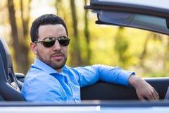 Schwarzer lateinamerikanischer Fahrer, der seinen Neuwagen fährt Stockfotografie