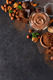 Schwarzer Lebensmittelhintergrund mit Kakao, Nüssen und Schokolade Stockfotos