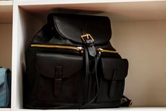 Schwarzer lederner Rucksack mit goldenen Rei?verschlusstaschen auf einem wei?en Regal im Speicher lizenzfreies stockfoto