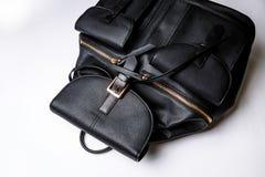 Schwarzer lederner Rucksack mit goldenen Rei?verschlusstaschen auf einem wei?en Hintergrund stockfotos
