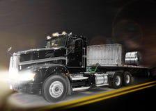 Schwarzer LKW, der durch die Elemente nachts rast Stockfotografie