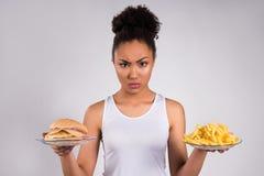 Schwarzer Mädchenholdingcheeseburger und -fischrogen stockfotografie