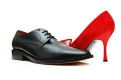 Schwarzer männlicher Schuh und rote Frau Stockbild