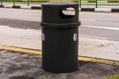 Schwarzer Mülleimer oder trashcan neben der Straße Stockfotos