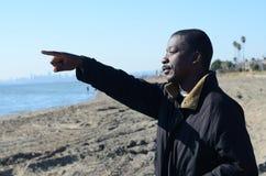 Schwarzer Mann, der auf den Ozean zeigt Lizenzfreies Stockbild