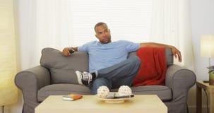 Schwarzer Mann, der auf der Couch fernsieht sitzt Stockfoto