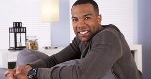 Schwarzer Mann, der auf der Couch lächelt an der Kamera stillsteht Lizenzfreie Stockfotos