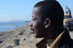 Schwarzer Mann, der in das Meer anstarrt Stockfotos