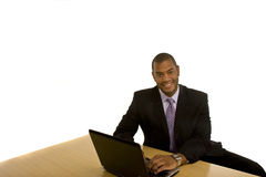 Schwarzer Mann, der an dem Laptop lächelt an der Kamera arbeitet lizenzfreie stockfotografie