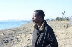 Schwarzer Mann, der in den Ozean anstarrt Lizenzfreie Stockfotografie