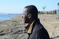 Schwarzer Mann, der in den Ozean anstarrt Lizenzfreies Stockbild