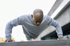 Schwarzer Mann der Eignung, den das Trainieren drücken, ups in städtischen Hintergrund stockfotos