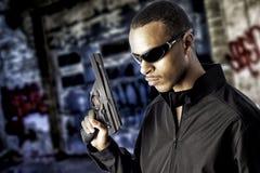 Schwarzer Mann, der eine Pistole anhält lizenzfreies stockbild